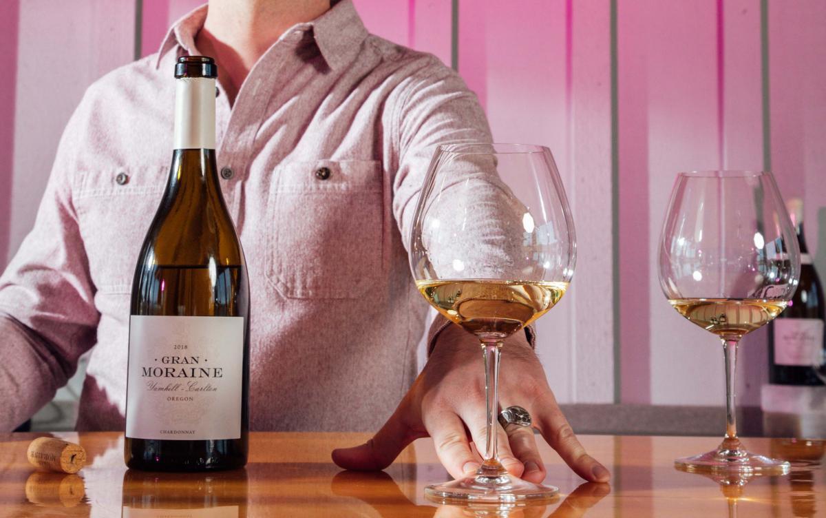 Man serving white wine behind a wine tasting bar