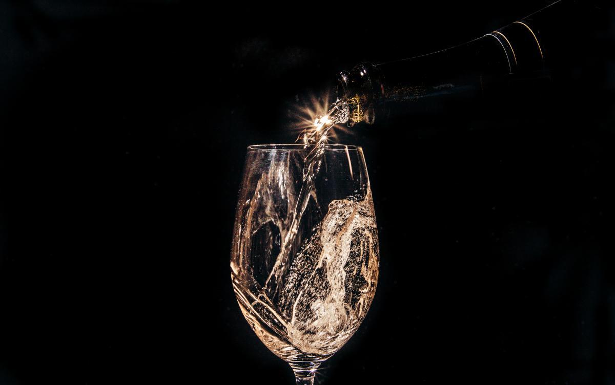 Blanc de Blanc in a glass against a black background