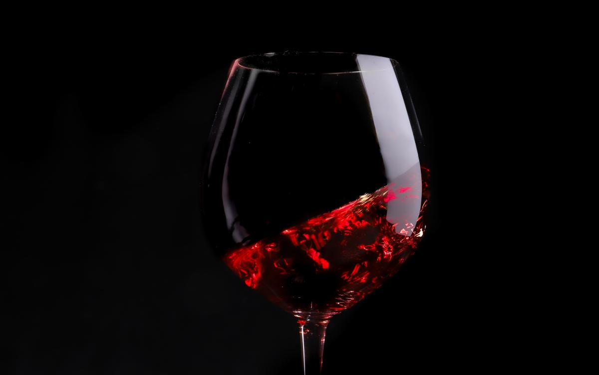 Pinot Noir swirling in a glass against a black background