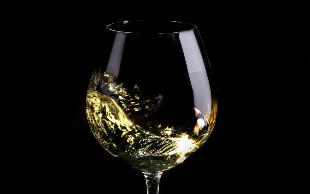 Chardonnay swirling in a glass against a black background