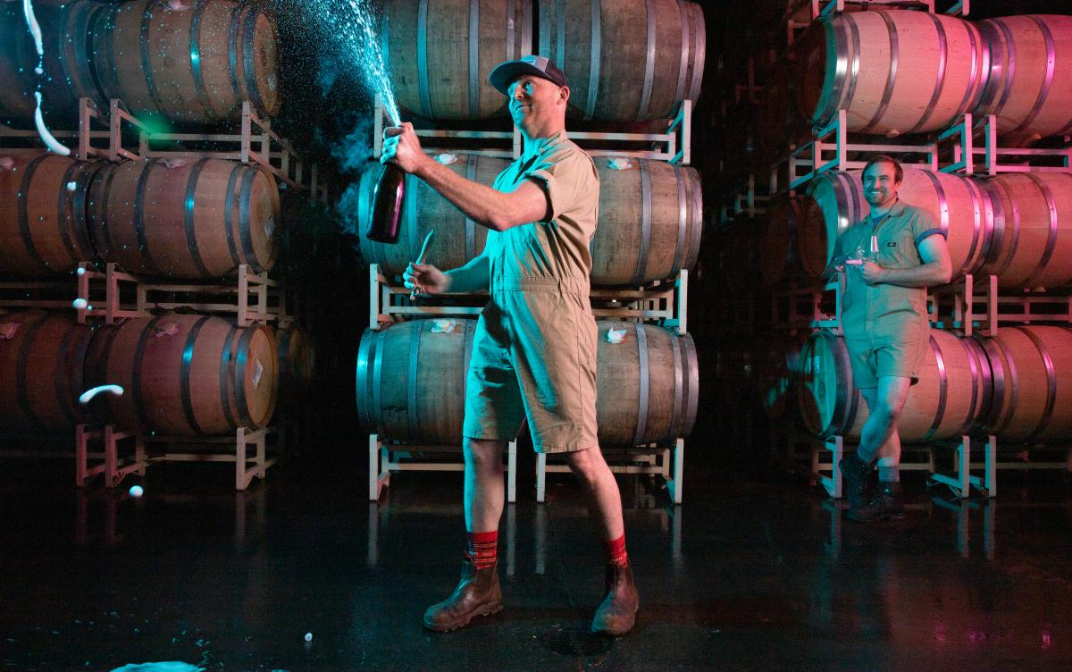 Man holding and opening a bottle of sparking wine spraying wine in the cellar