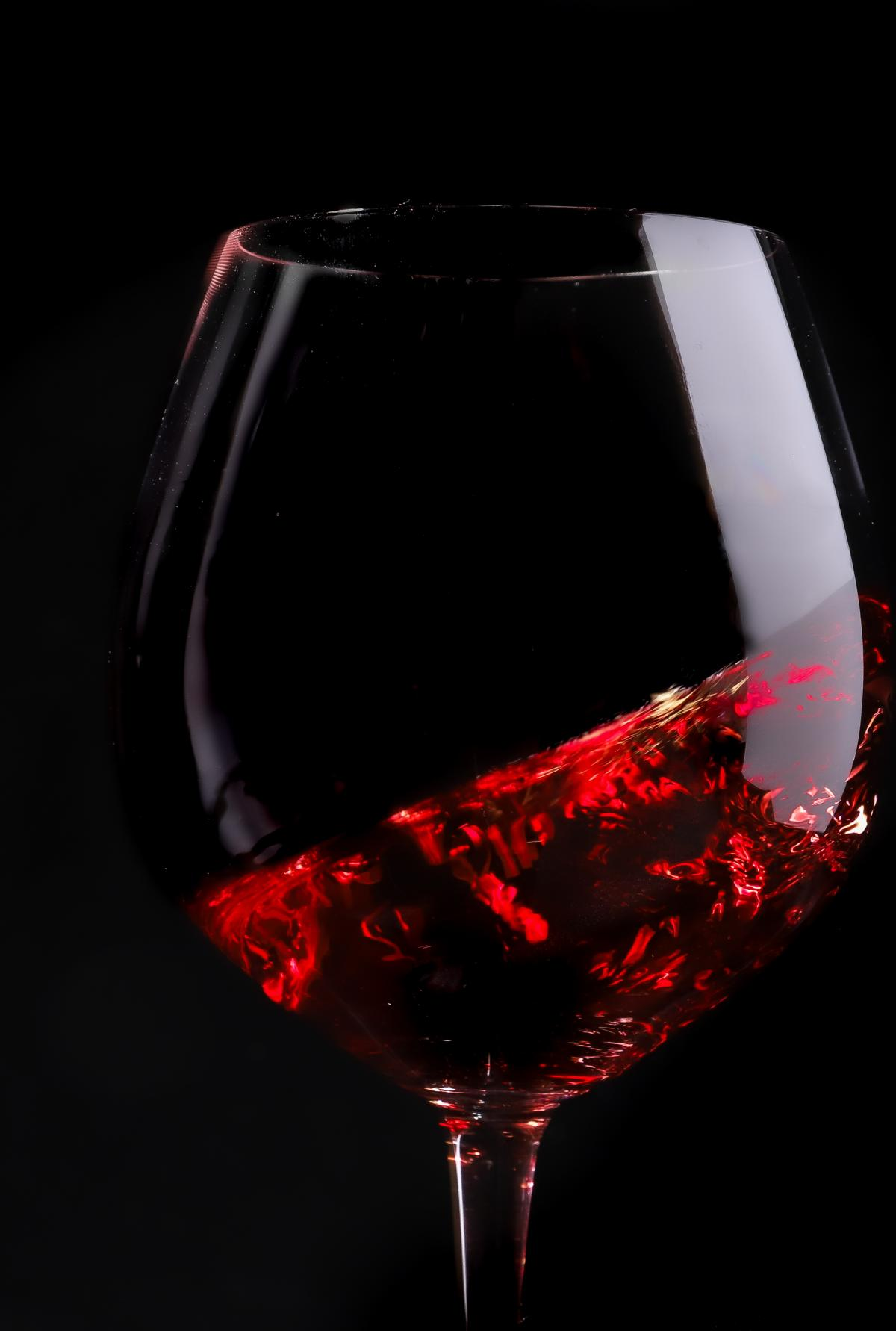 Swirling glass of Dropstone Pinot Noir against a black background