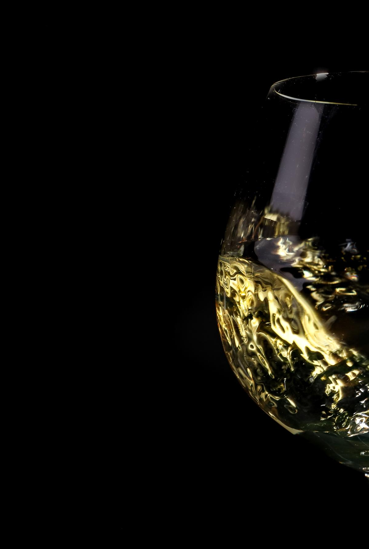 White wine swirling in a glass against a dark background