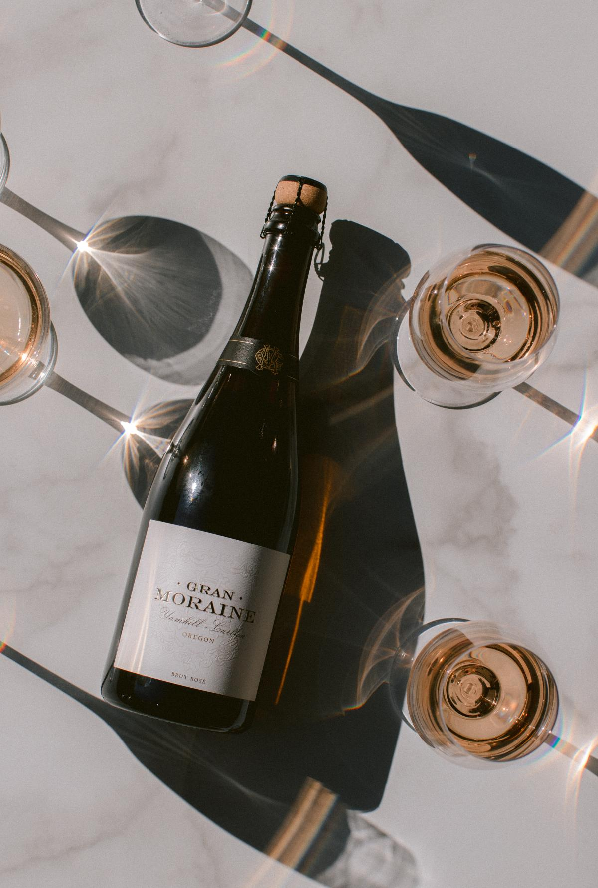 From above, a bottle of Brut Rosé laying on a table surrounded by wine glasses