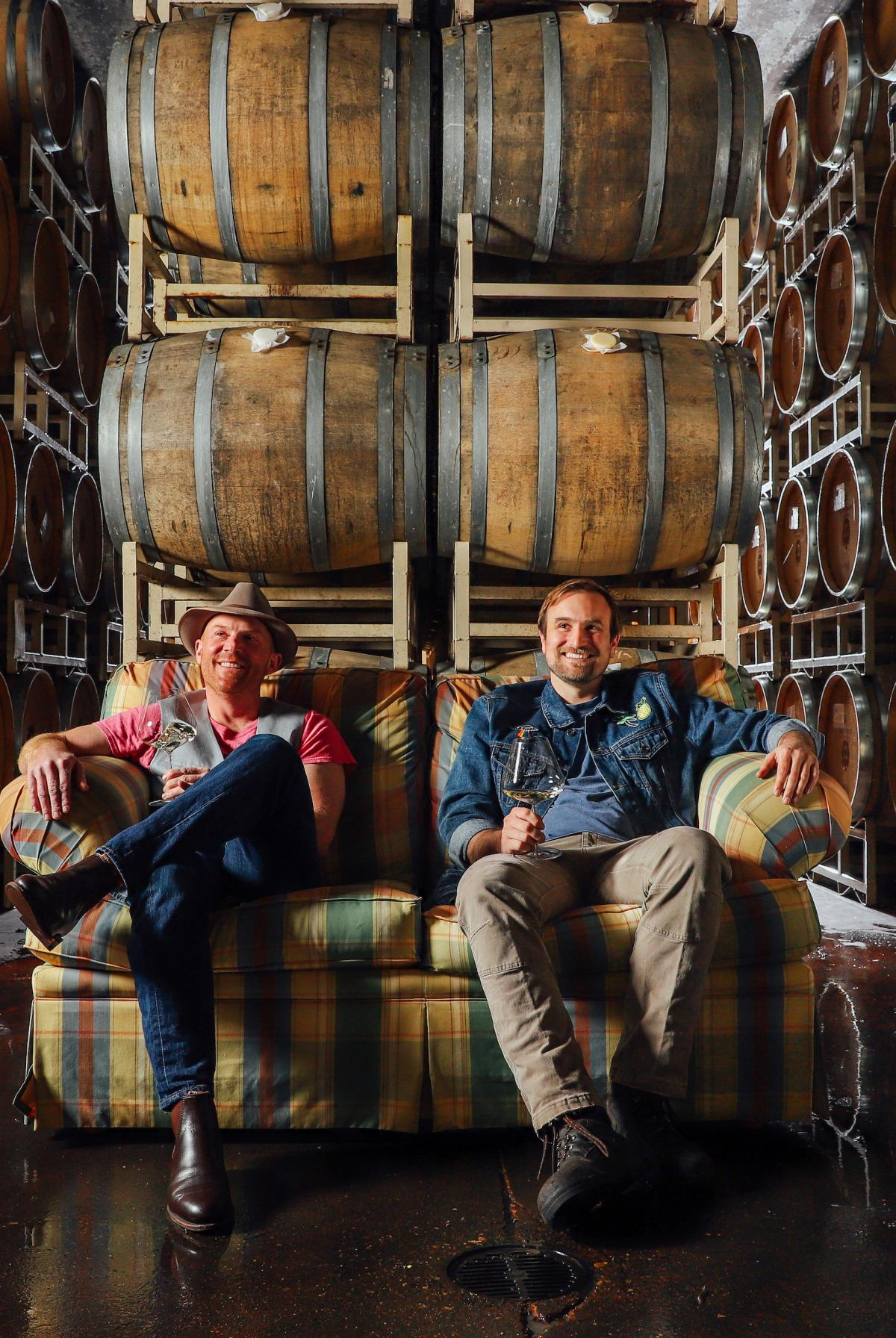 Shane and Myles holding wine glasses sitting on a plaid couch in the cellar