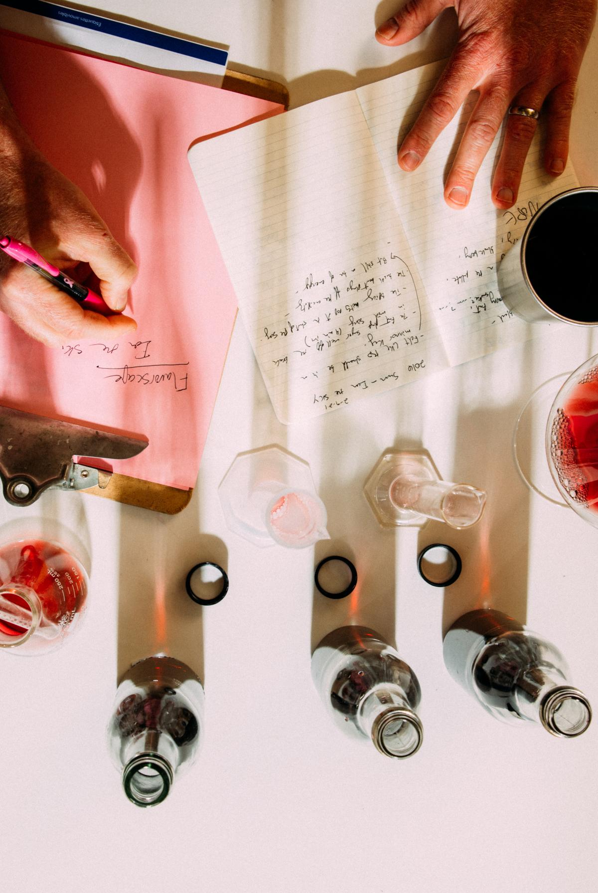 Overhead shot of a person taking lab notes with wine blending beakers around the perimeter