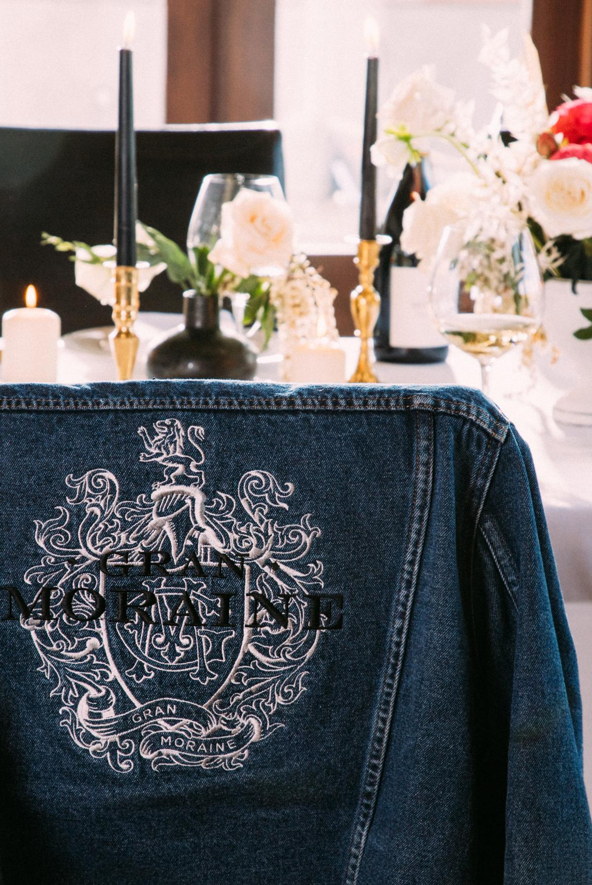 Embroidered jean jacket with Gran Moraine logo on the back of chair at a decorated table