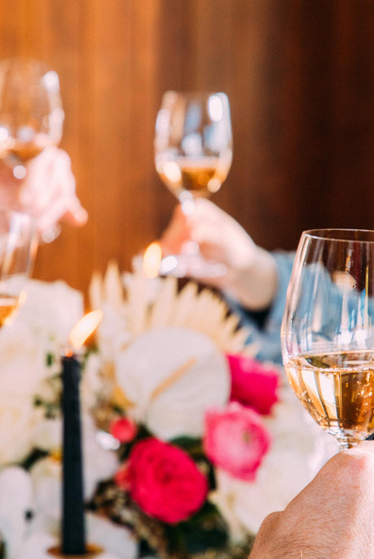 Gathering of people around a table with flowers all holding up glasses of white wine